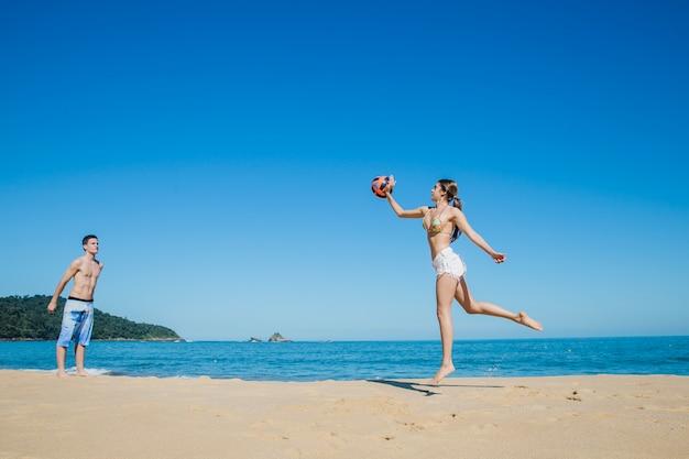Mann und frau spielen beach-volleyball Kostenlose Fotos