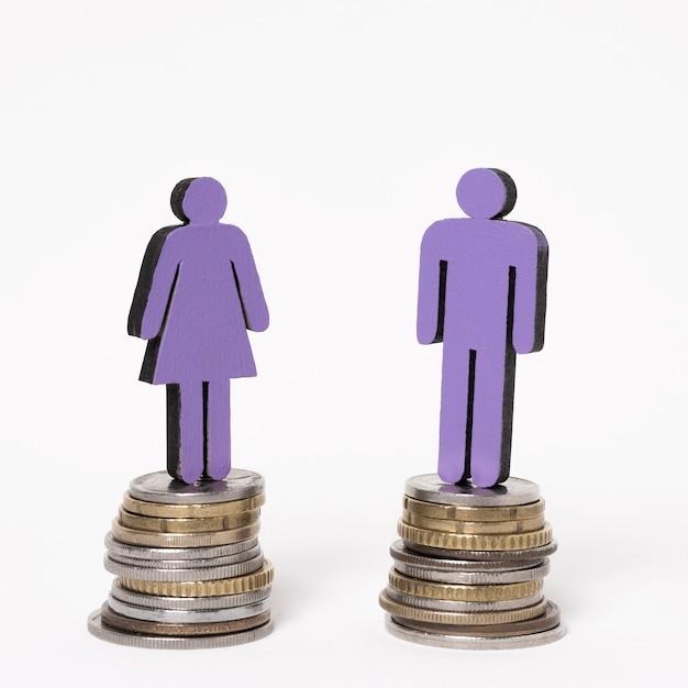 Mann und frau stehen auf gleichen haufen münzen Kostenlose Fotos