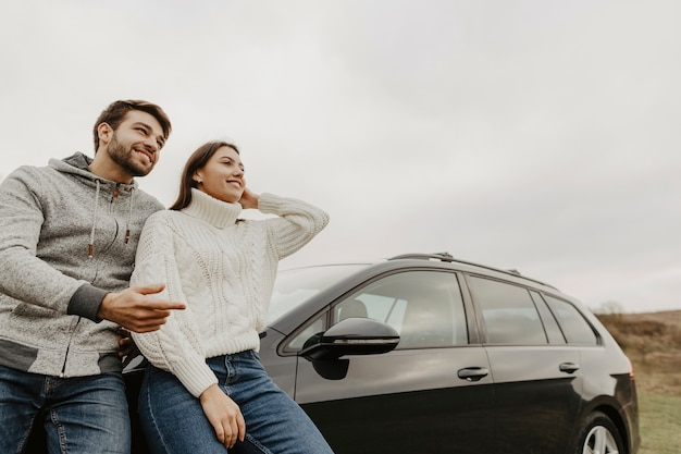 Mann und frau stützte sich auf das auto Kostenlose Fotos