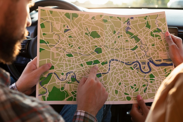 Mann und frau überprüfen eine karte im auto Kostenlose Fotos