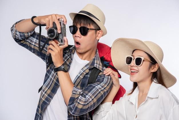 Mann und frau zogen sich an, um zu reisen, eine brille zu tragen und fotos zu machen Kostenlose Fotos