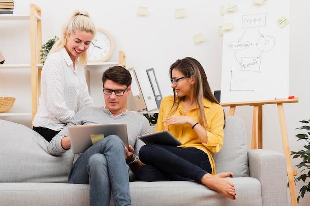 Mann und frauen, die auf sofa sitzen und an laptop arbeiten Kostenlose Fotos