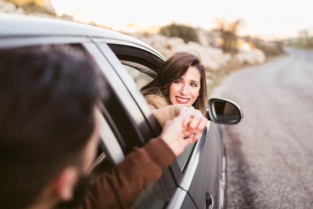 Mann- und frauenhändchenhalten außerhalb des autos Kostenlose Fotos