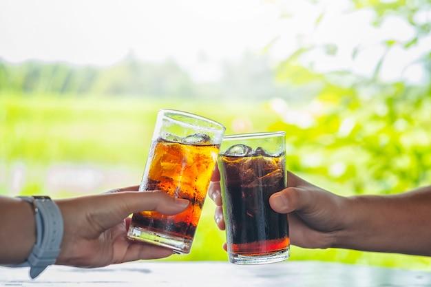 Mann- und frauenhand, die glas cola gibt. Premium Fotos