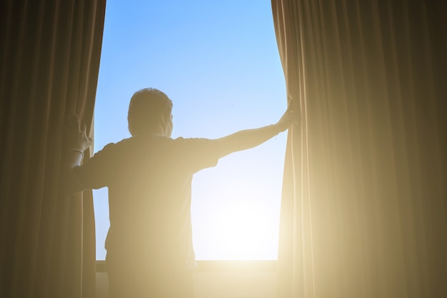 Mann und hoffnung konzept. mann, der fenstervorhänge öffnet Premium Fotos