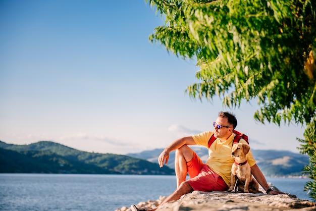 Mann und hund sitzen auf einem steinernen dock am meer Premium Fotos