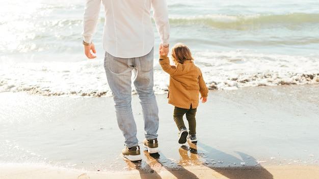 Mann und kleiner junge stehen am meer Kostenlose Fotos
