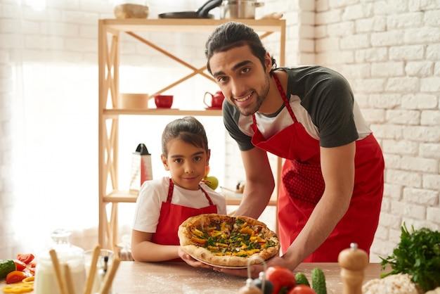Mann und mädchen gekochte pizza auf küche Premium Fotos