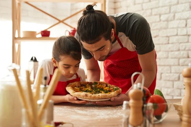 Mann und mädchen kochten schöne pizza auf küche. Premium Fotos