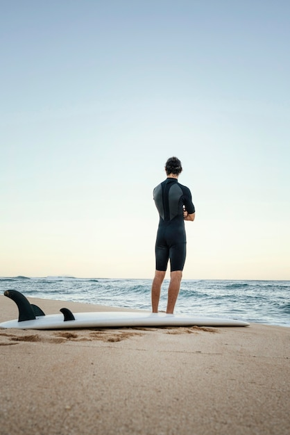 Mann und surfbrett am meer Kostenlose Fotos