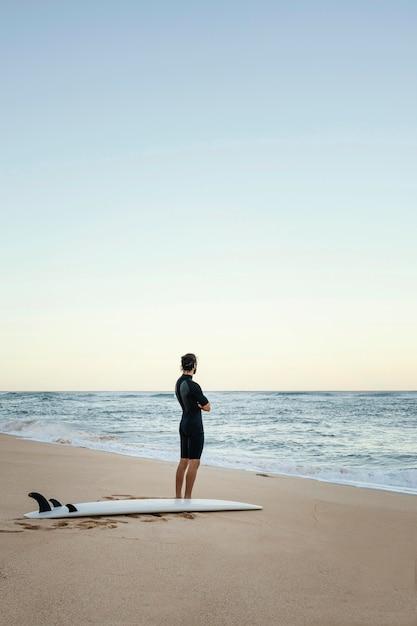Mann und surfbrett am ozean long shot Kostenlose Fotos