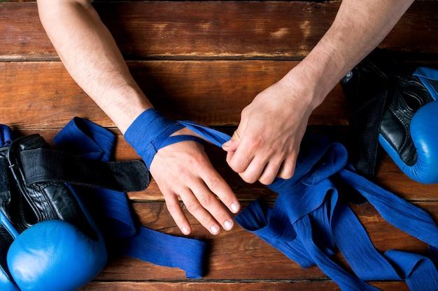 Mann verband boxband auf seinen händen vor dem boxkampf auf einer holzoberfläche. das konzept des trainings für boxtraining oder kampf. flache lage, draufsicht Premium Fotos