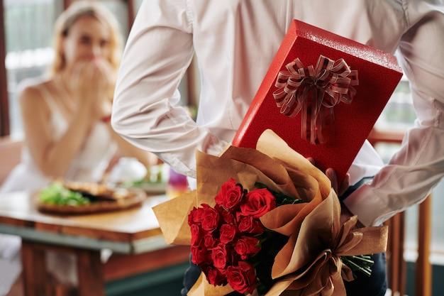 Mann versteckt strauß rosen und geschenkbox hinter seinem rücken als geburtstagsgeschenk für freundin Premium Fotos