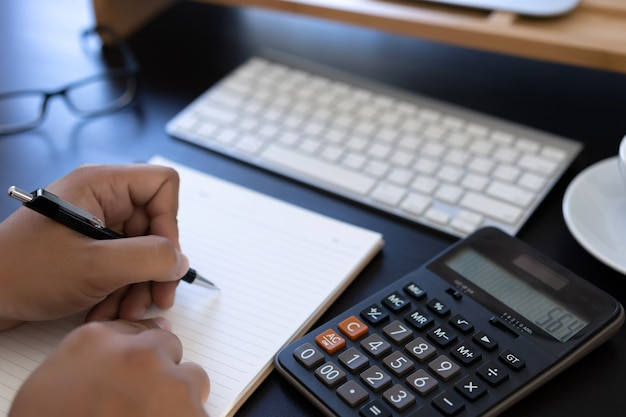 mann verwendet rechner um die kosten im b ro zu berechnen. Black Bedroom Furniture Sets. Home Design Ideas
