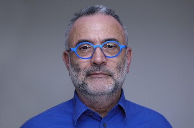 Mann von mittlerem alter mit blauem hemd und gläsern Premium Fotos