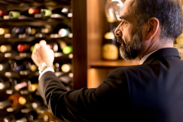 Mann wählt eine flasche wein Premium Fotos