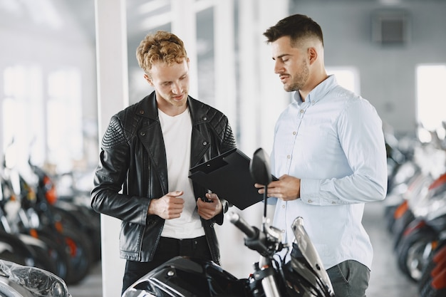 Mann wählte motorräder im motoladen. mann in einer schwarzen jacke. manager mit client. Kostenlose Fotos