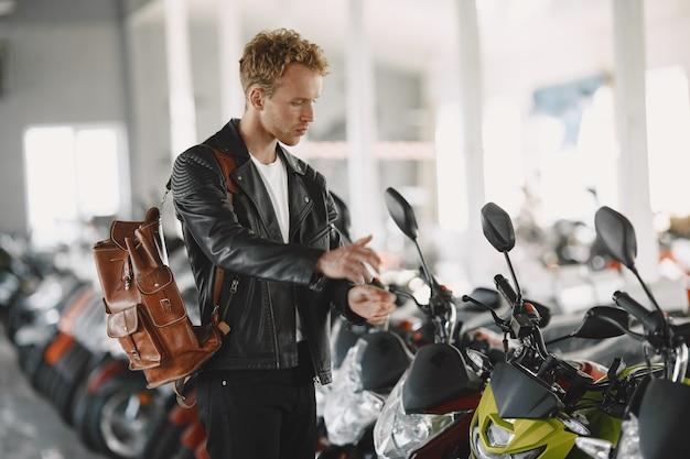 Mann wählte motorräder im motoladen. mann in einer schwarzen jacke. Kostenlose Fotos
