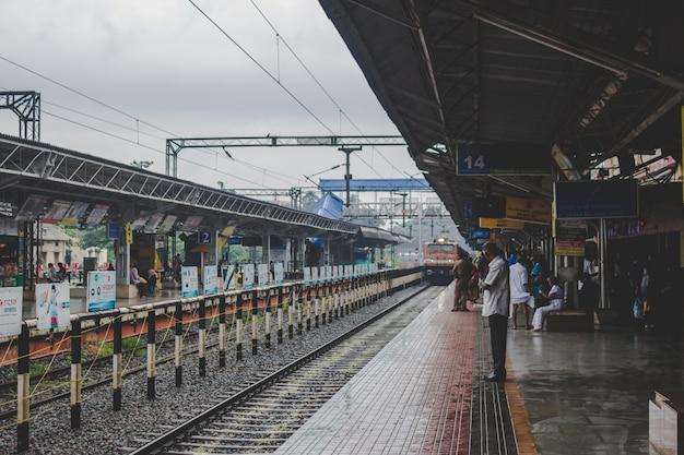 Mann wartet auf seinen Zug Kostenlose Fotos