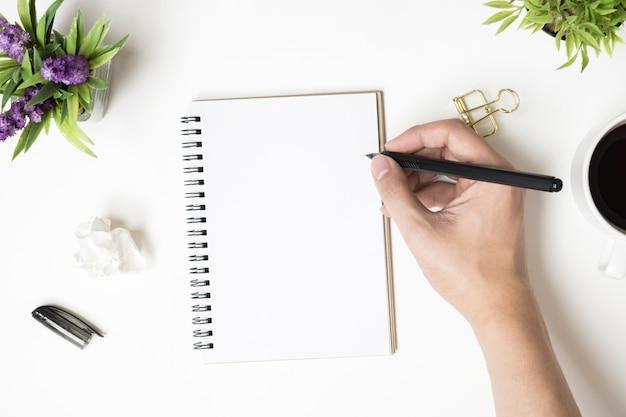 Mann wird etwas auf leere notizbuchseite schreiben. draufsicht, flach zu legen. Premium Fotos