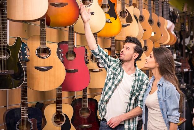 Mann zeigt der mädchengitarre in einem musikgeschäft. Premium Fotos