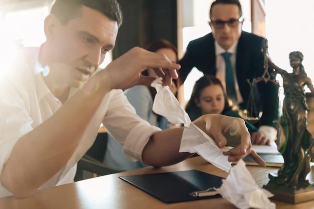 Mann zerreißt ehevertrag beim sitzen neben frau Premium Fotos