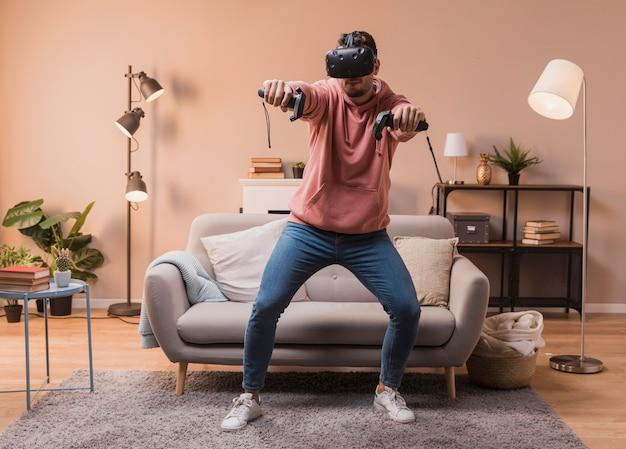 Mann zu hause, der mit virtuellem kopfhörer spielt Kostenlose Fotos