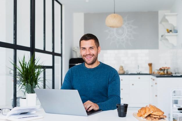 Mann zu hause unter verwendung des laptopmodells Kostenlose Fotos