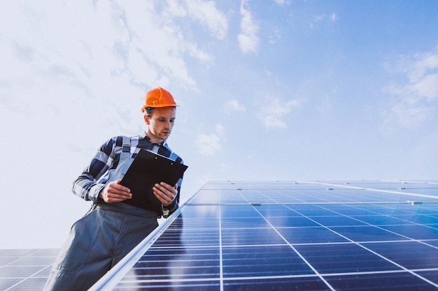 Mannarbeitskraft im firld durch die sonnenkollektoren Kostenlose Fotos