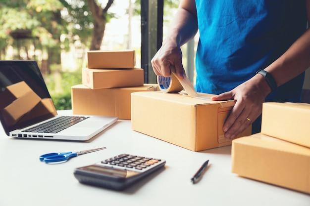 Mannarbeitskraft-zustelldienst und arbeitsverpackungskasten, geschäftseigentümerfunktion, die bestellung überprüft, um vor dem senden des kunden in der post, versand-online-verkäufe zu bestätigen Premium Fotos