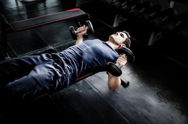 Mannaufnahme dumbell in der turnhalle. übung mit trainingsprogramm für gesundes Premium Fotos