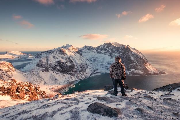 Mannbergsteiger, der auf schneebedecktem berg bei sonnenuntergang steht Premium Fotos