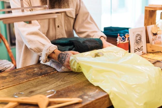Mannbesitzer am tresen packen die klamotten in gelbe plastiktüte Kostenlose Fotos
