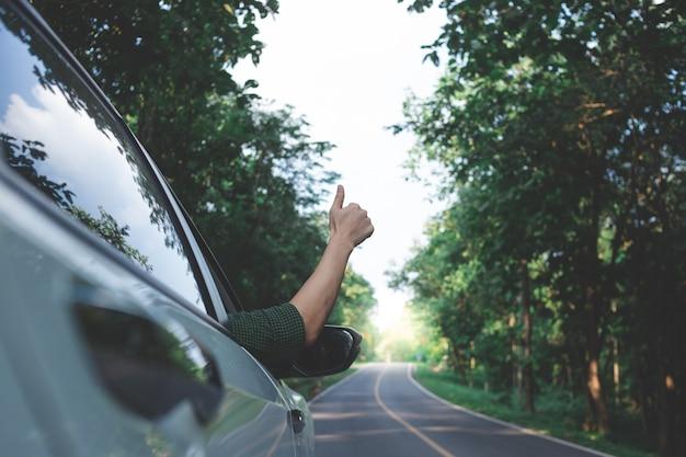 Mannfahrer, der den wind durch seine hände beim fahren in die landseite glaubt. Premium Fotos