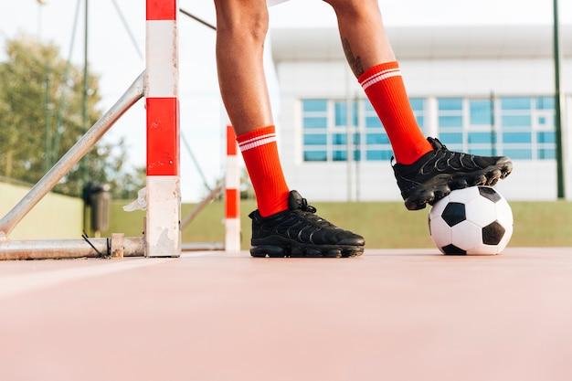 Mannfüße, die fußball am stadion treten Kostenlose Fotos