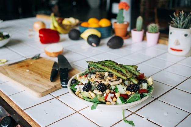 Mannhände, die großen tiefen teller voll des gesunden paläo-vegetarischen salats halten, der aus frischen biologischen biologischen bestandteilen, gemüse und früchten, beeren und anderen ernährungsphysiologischen dingen hergestellt wird Kostenlose Fotos