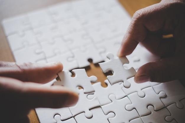 Mannhände, die paarpuzzlespielstück im büro anschließen. ziele und strategie Premium Fotos