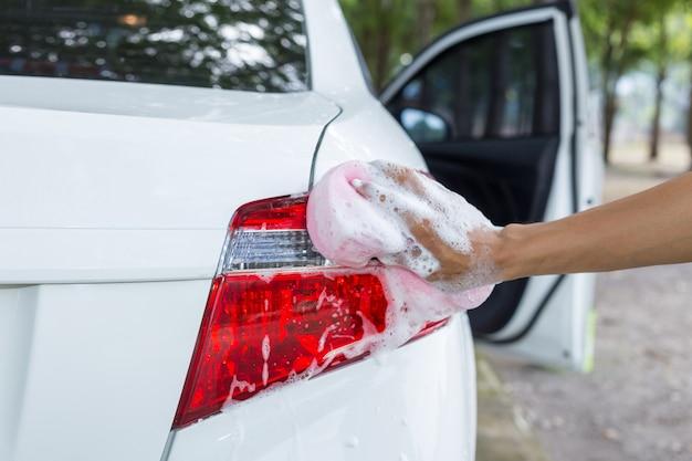 Mannhände halten schwamm für das waschen des weißen autos Premium Fotos