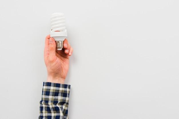 Mannhand, die energiesparende glühlampe hält Kostenlose Fotos