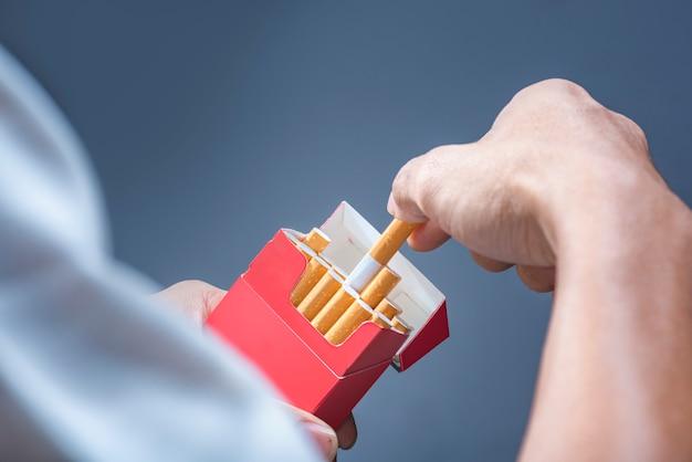 Mannhand nehmen eine zigarette vom roten zigarettensatz Premium Fotos
