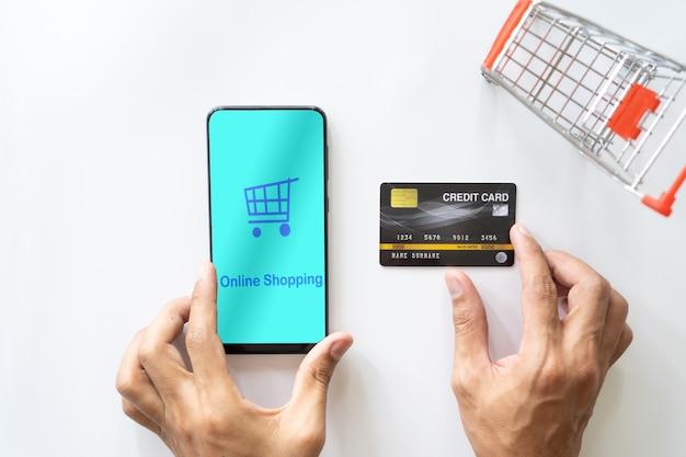 Mannhand unter verwendung des mobilen smartphone und der kreditkarte. online einkaufen Premium Fotos