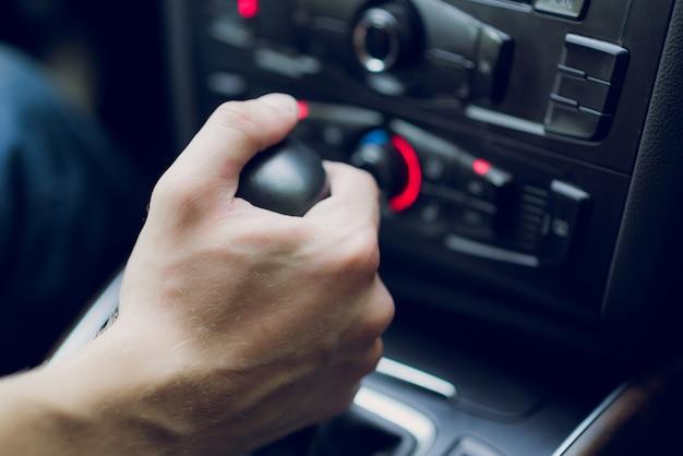 Mannhand verschiebt getriebe im autosalon. nahansicht Premium Fotos