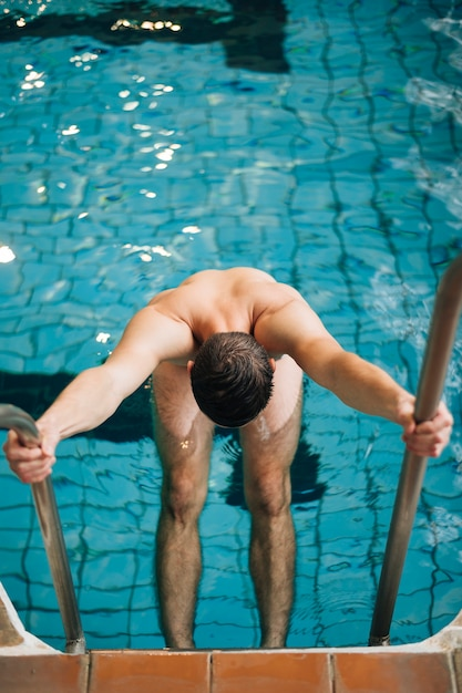 Mannholding des hohen winkels weg von der schwimmbadtreppe Kostenlose Fotos