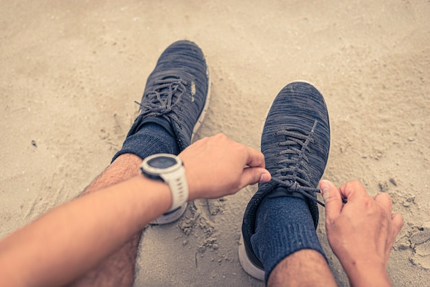 Mannläufer, der die spitze bereit bindet, auf strand zu laufen Premium Fotos