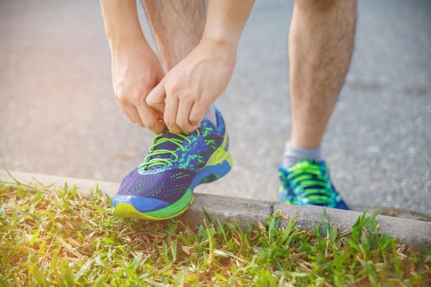 Mannläufer, der morgens laufschuhe vor lauf für übung bindet. mannläufer, der schuh überprüft, um fertig zu werden zu laufen. Premium Fotos