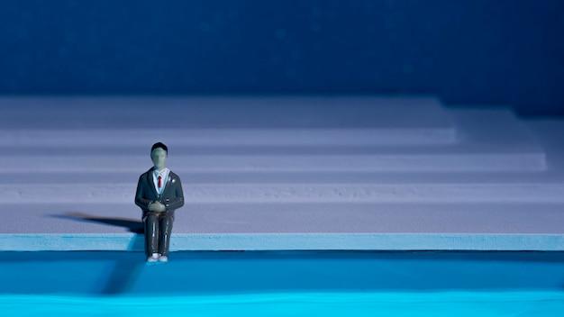 Mannpuppe, die neben schwimmbad mit kopienraum sitzt Kostenlose Fotos