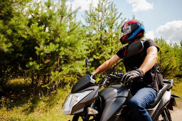 Mannreitmotorrad auf schotterweg mit sturzhelm Premium Fotos