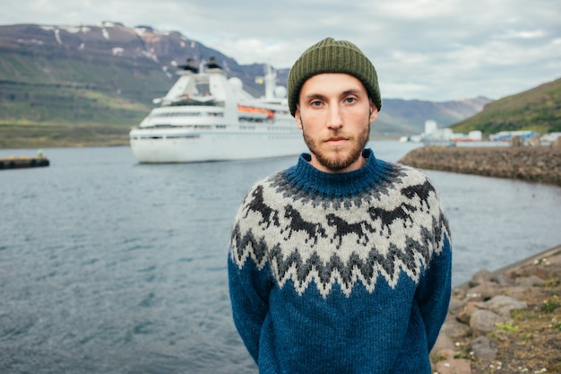 Mannsegler im traditionellen pulloverstand im fjordhafen Kostenlose Fotos
