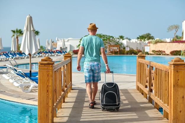 Manntourist im sommer kleidet mit einem koffer in seiner hand und betrachtet das meer auf dem strand Premium Fotos