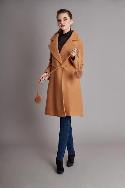 Mantel des modemädchens im frühjahr auf grauem hintergrund Premium Fotos